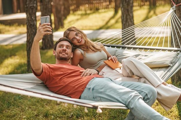 Giovane uomo e donna allegri che prendono selfie