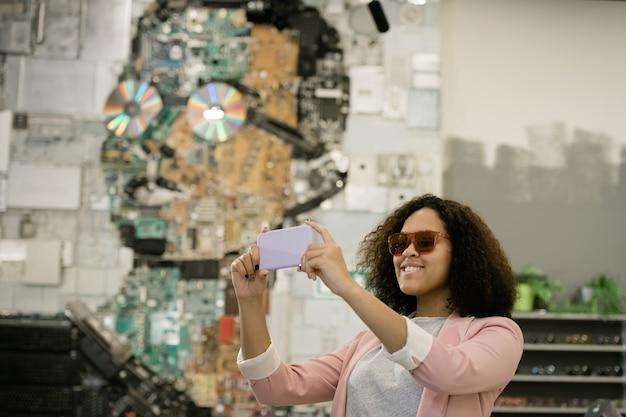 Giovane femmina allegra di razza mista in occhiali da sole utilizza lo smartphone mentre fa selfie nel negozio di ottica contemporanea