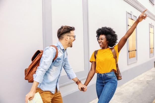 Giovane coppia allegra felicissima che cammina per strada e si diverte. uomo che tiene una mappa. concetto di turismo.