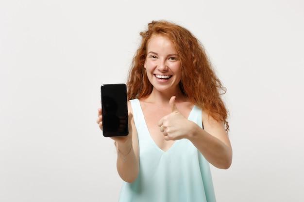 Giovane ragazza allegra della donna della testarossa in vestiti leggeri casuali che posano isolati su fondo bianco. concetto di stile di vita della gente. mock up copia spazio. mostrando pollice in su tenere il telefono cellulare con schermo vuoto vuoto.