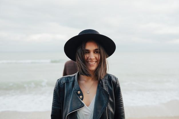 Giovane ragazza sorridente allegra in elegante giacca nera e cappello sulla spiaggia del mare.