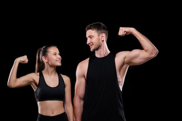 Giovane coppia di sport allegri in abbigliamento sportivo che si guardano mentre mostrano la loro forza