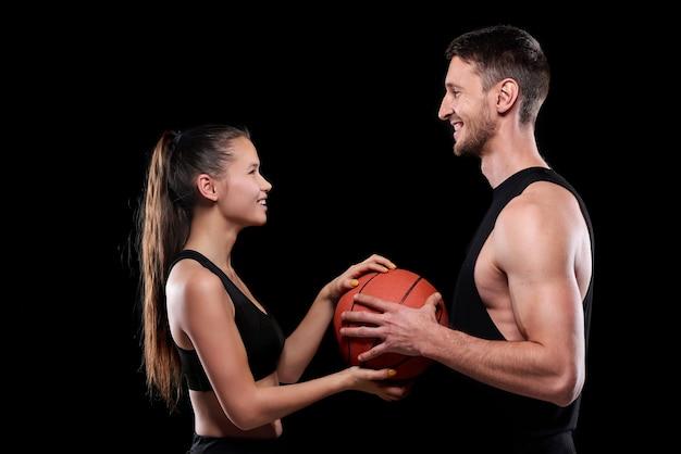 Giovane coppia sportiva allegra in activewear tenendo palla mentre in piedi uno di fronte all'altro