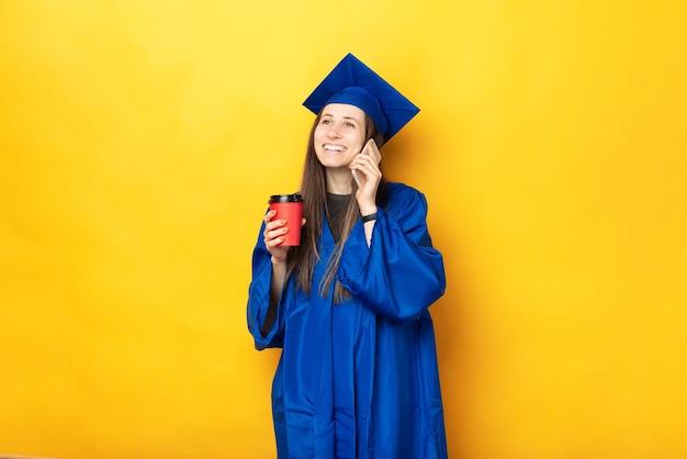 Un giovane studente allegro in uniforme da laurea sta parlando felicemente al telefono e sta bevendo una bevanda calda