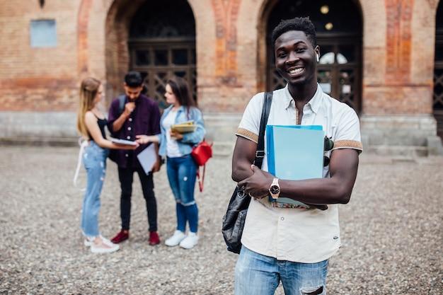 Giovane studente nerd africano allegro di successo in piedi con i libri i suoi compagni di classe