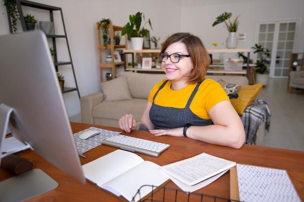 Giovane insegnante allegra in occhiali e abbigliamento casual guardando il suo studente online sullo schermo del computer durante la consultazione da casa
