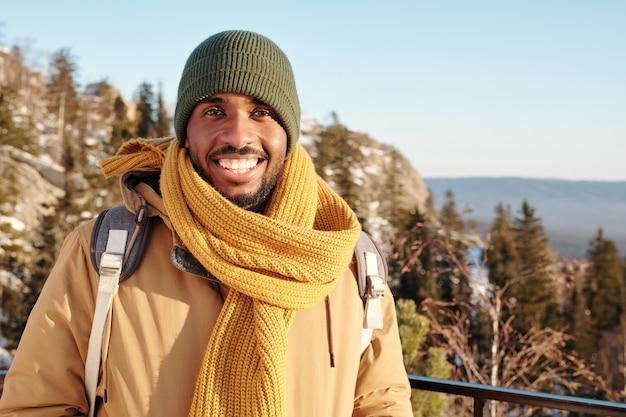 Giovane viaggiatore allegro con lo zaino che si gode l'avventura invernale