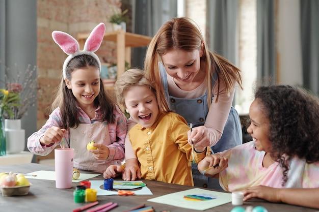 Giovane donna allegra che si china sul tavolo con un gruppo di bambini felici mentre li aiuta a dipingere l'immagine dell'uovo di pasqua prima delle vacanze