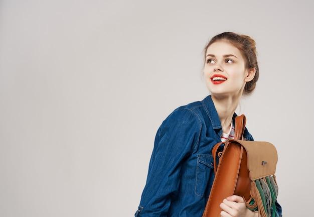 Giovane donna allegra nello stile di vita dello studente dello zaino dei vestiti di modo