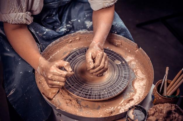 Giovane e allegra donna mostra come lavorare con l'argilla e la ruota di ceramica