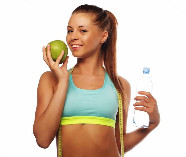 Giovane donna allegra in abbigliamento sportivo con mela e acqua, isolato su bianco
