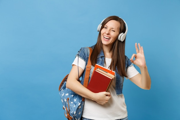 La giovane studentessa allegra in vestiti del denim con le cuffie dello zaino ascolta i libri di scuola della tenuta della musica che mostrano il segno giusto lampeggiante isolato su priorità bassa blu. istruzione al college universitario di scuola superiore.