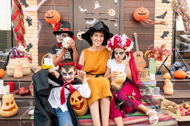 Giovane donna allegra in cappello della strega e vestito giallo che si siede sulla scala tra i bambini spettrali di halloween circondati da mele e zucche mature
