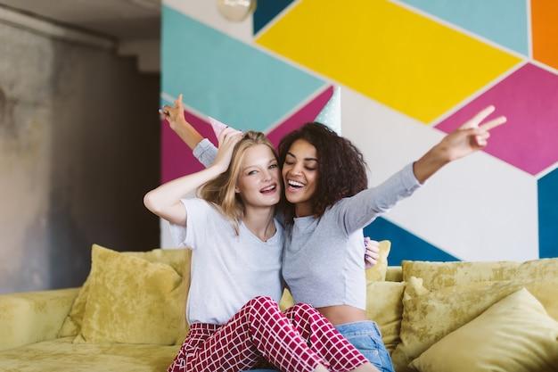 Giovane donna allegra con capelli biondi in protezione di compleanno e bella donna afro-americana con i capelli ricci scuri che trascorrono felicemente del tempo insieme al muro colorato a casa