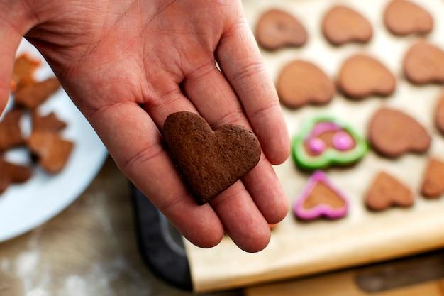 Un giovane chef decora i biscotti di pan di zenzero con glassa rosa, disegna gli occhi e la bocca. concetto di cottura