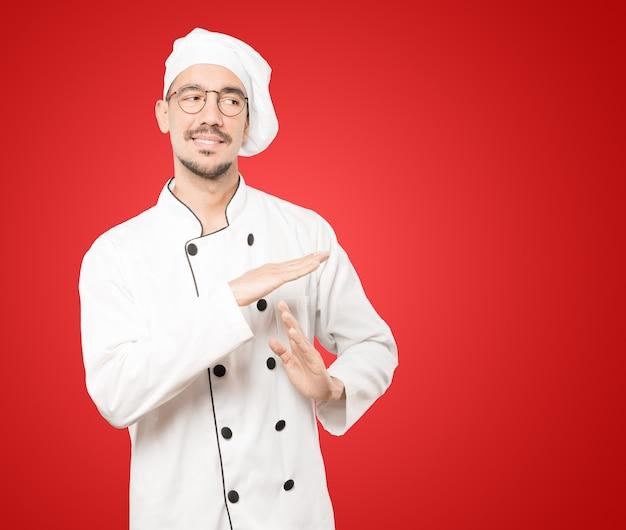 Giovane chef facendo un gesto di timeout con le mani