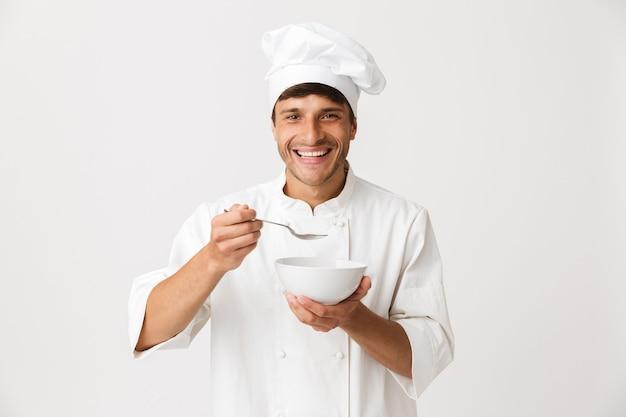 Il giovane uomo del cuoco unico mangia isolato sul piatto bianco della tenuta della parete.