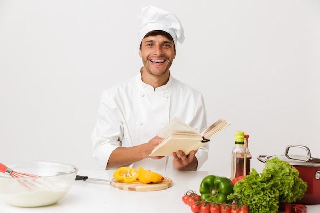 Giovane chef uomo isolato sulla parete bianca che cucina libro di lettura.