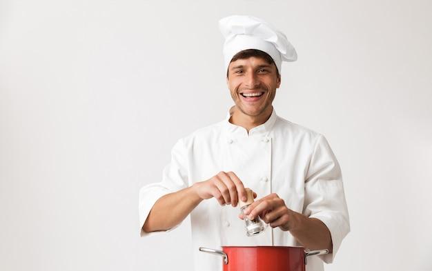 Giovane uomo del cuoco unico isolato sulla cucina bianca della parete.