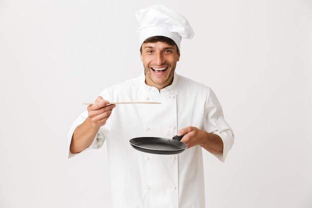 Giovane chef uomo in piedi isolato su muro bianco tenendo le stoviglie.