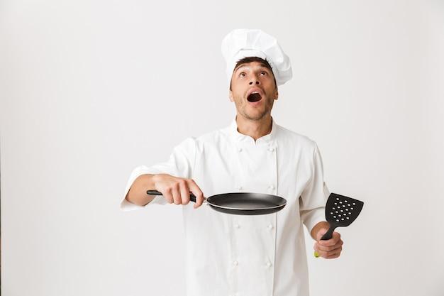 Giovane chef uomo in piedi isolato sulla parete bianca che tiene la padella che cucina.
