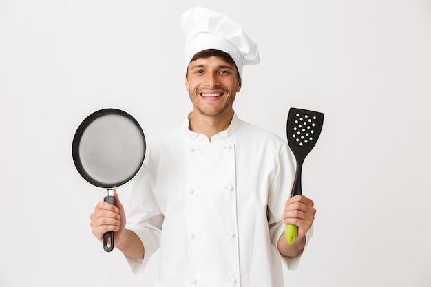 Giovane chef uomo in piedi isolato sulla parete bianca che tiene la padella.