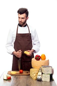 Giovane chef con formaggi isolati sul muro bianco, pubblicità di formaggio
