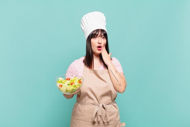 Giovane chef donna che si sente scioccata e spaventata, sembra terrorizzata con la bocca aperta e le mani sulle guance