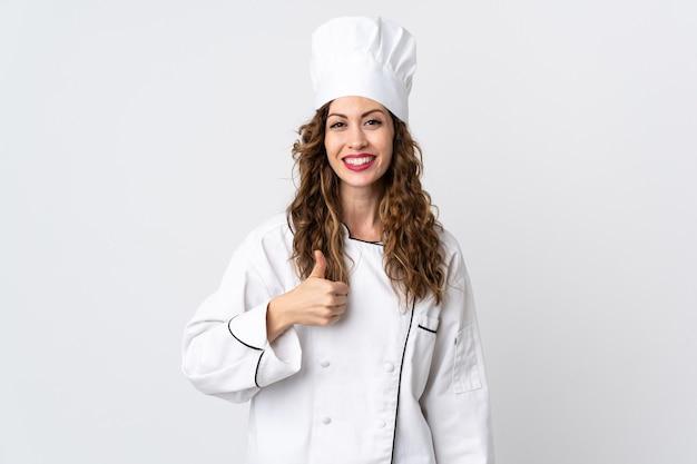La giovane donna del cuoco unico isolata sulla parete bianca che dà i pollici aumenta il gesto