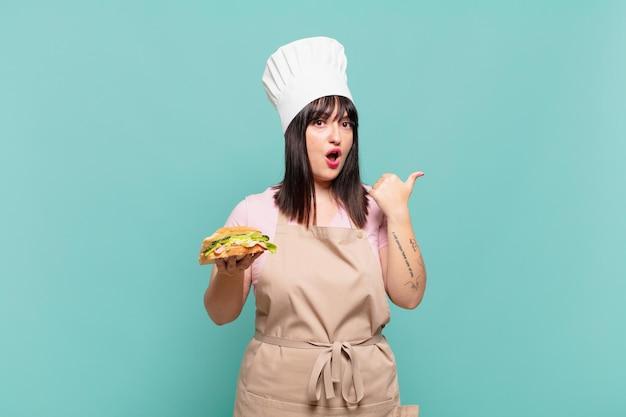 Giovane chef donna che sembra stupita per l'incredulità, indicando un oggetto sul lato e dicendo wow, incredibile