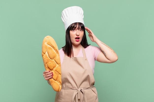 Giovane chef donna che sembra felice, stupita e sorpresa, sorridente e realizzando una buona notizia incredibile e incredibile