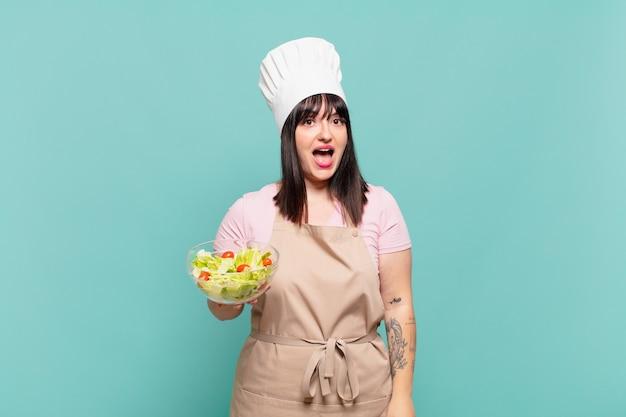 Giovane chef donna che sembra felice e piacevolmente sorpresa, eccitata con un'espressione affascinata e scioccata