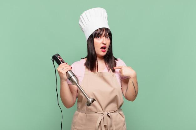 Giovane chef donna che sembra scioccata e sorpresa con la bocca spalancata, che indica se stessa