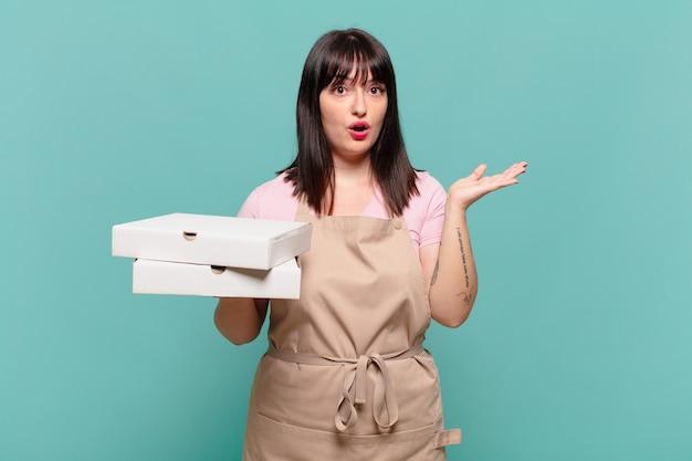 Giovane chef donna che sembra sorpresa e scioccata, con la mascella caduta in possesso di un oggetto con una mano aperta sul lato