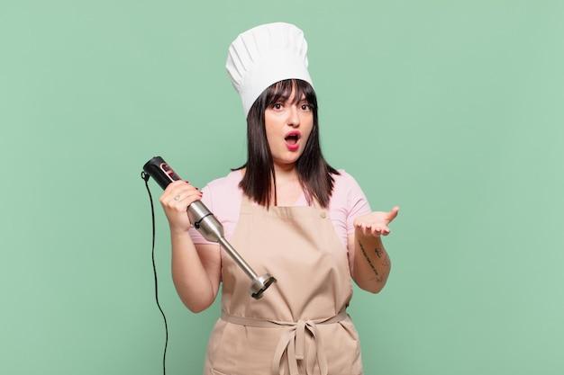 Giovane chef donna a bocca aperta e stupita, scioccata e stupita da un'incredibile sorpresa