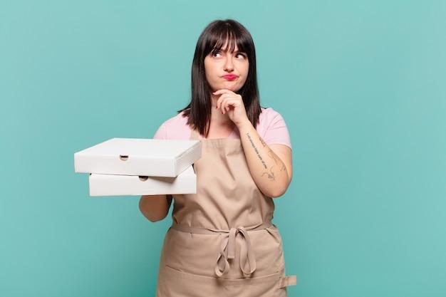 Giovane chef donna che pensa, si sente dubbiosa e confusa, con diverse opzioni, chiedendosi quale decisione prendere