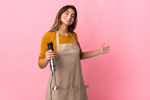 Donna giovane chef utilizzando frullatore a immersione isolato