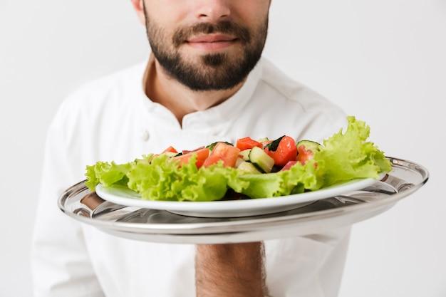Giovane capo uomo in uniforme da cuoco piatto profumato mentre si tiene piatto con insalata di verdure isolato su muro bianco