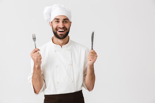 Giovane capo in uniforme da cuoco che sorride mentre tiene in mano un cucchiaio e una forchetta di metallo isolati su un muro bianco