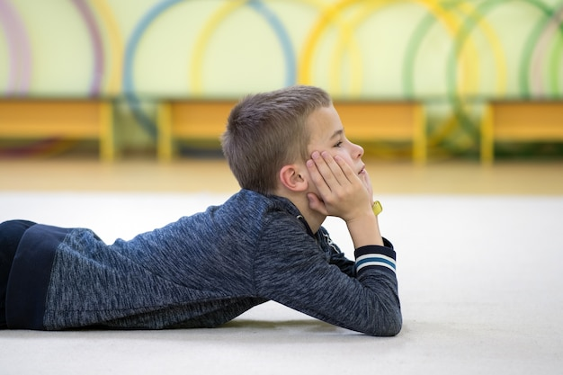 Ragazzo del bambino in giovane età che stabilisce e relaxiong mentre riposa sul pavimento all'interno della sala sportiva in una scuola dopo l'allenamento.