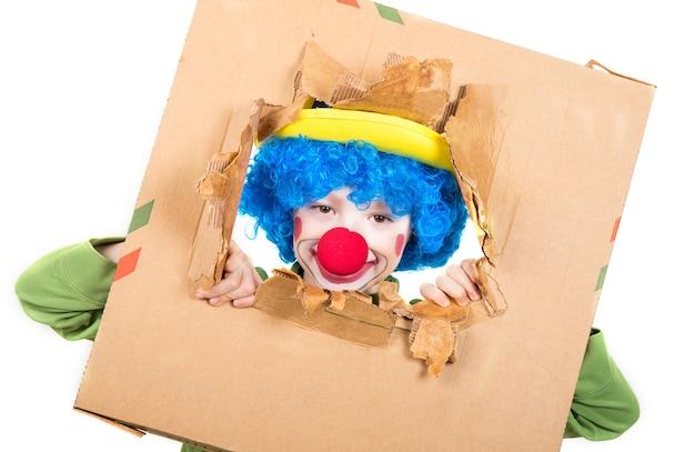 Un bambino vestito da clown con parrucca e naso finto si diverte a guardare dal cartone aperto