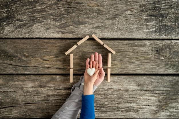 Bambino piccolo e suo padre che indicano il loro amore per una casa in un'immagine concettuale con le loro mani che tengono un cuore all'interno della cornice di una casa.