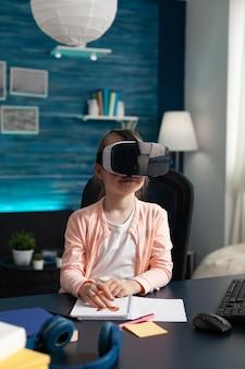 Corso di lezione di apprendimento per bambini piccoli con gadget tecnologici per occhiali vr alla scrivania di casa. studentessa intelligente che utilizza apparecchiature di visione per il metodo di studio dell'intrattenimento della scuola elementare