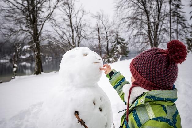 Bambino in giovane età che fa un pupazzo di neve di inverno