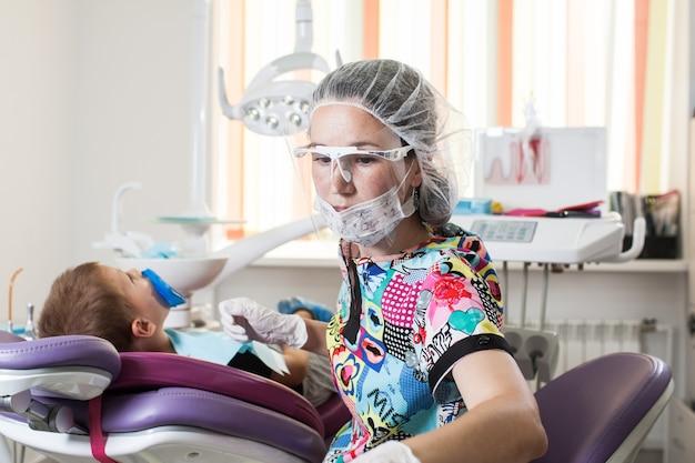 Il dentista medico dei bambini piccoli tratta i denti con dispositivi diversi