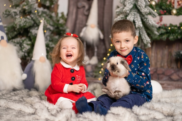 Per i bambini piccoli, babbo natale ha regalato un soffice coniglio per natale. vacanze in famiglia, racconto di natale