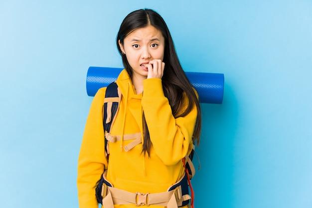 Unghie mordaci isolate giovane donna cinese di viaggiatore con zaino e sacco a pelo, nervose e molto ansiose.