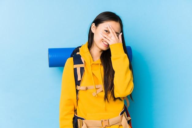 Giovane donna cinese zaino in spalla isolato sbattere le palpebre alla telecamera attraverso le dita, imbarazzato che copre il viso.