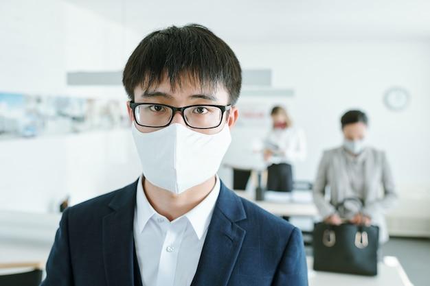 Giovane uomo d'affari cinese in occhiali da vista, maschera protettiva e vestito con i suoi colleghi da scrivanie
