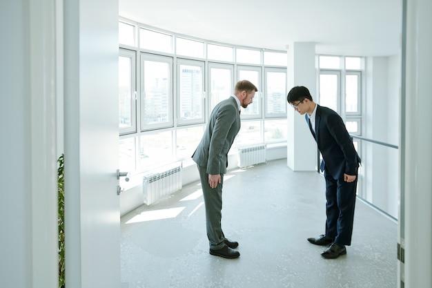 Giovani uomini d'affari cinesi e caucasici in abiti da cerimonia che si inchinano l'un l'altro durante il saluto mentre si trovano all'interno di un grande edificio per uffici